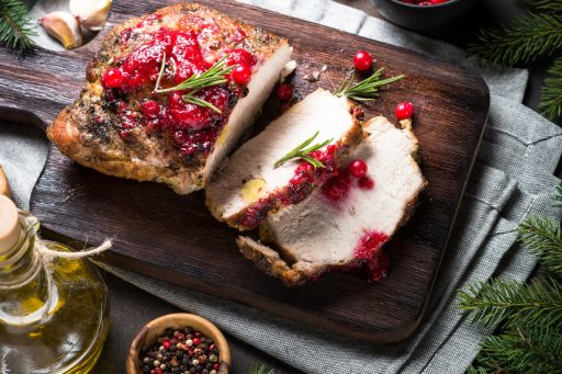 Baked pork meat with cranberry sauce. Christmas Winter meat recipe. Christmas food.