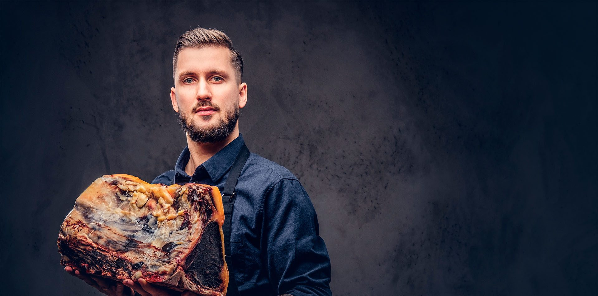 Professional butcher with raw smoked meat in a studio.