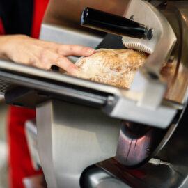 Close-up of female butcher cutting york ham in a cutting machine inside a butcher shop.