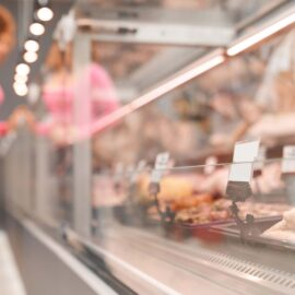 Side view of fasionable lady with curly hair looking and choosing fresh meat in store. Selective focus of store counter with big assortment of raw meat products in supermarket.